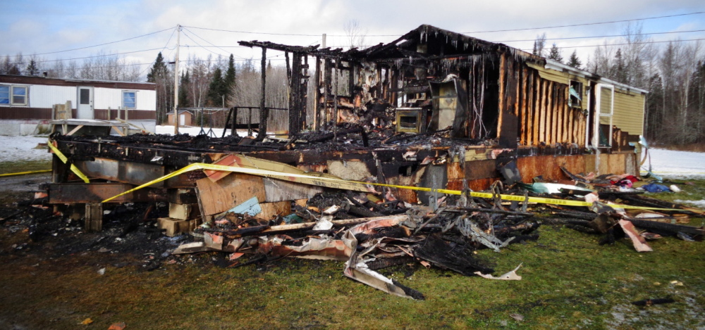 The remains of a mobile home in which four people died Thursday are cordoned off by police tape in Caribou, in this photo provided by Maine State Police.