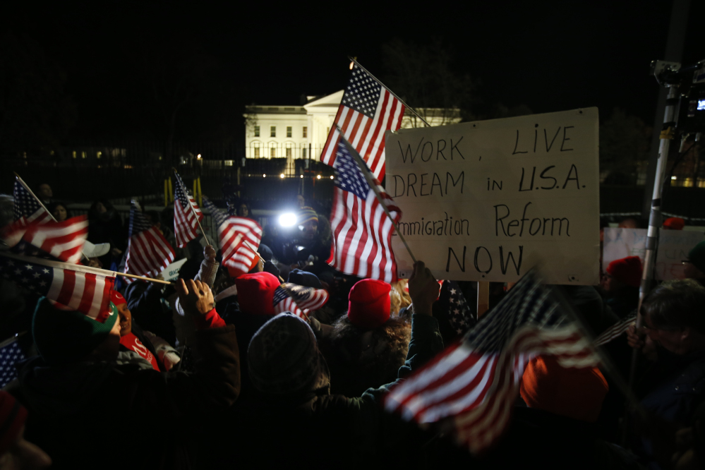 "Rally participants wave American flags and signs in front of the White House on Thursday before President Obama's announcement of far-reaching orders on immigration that will allow nearly 5 million people now in the U.S. illegally to ""come out of the shadows and get right with the law."""