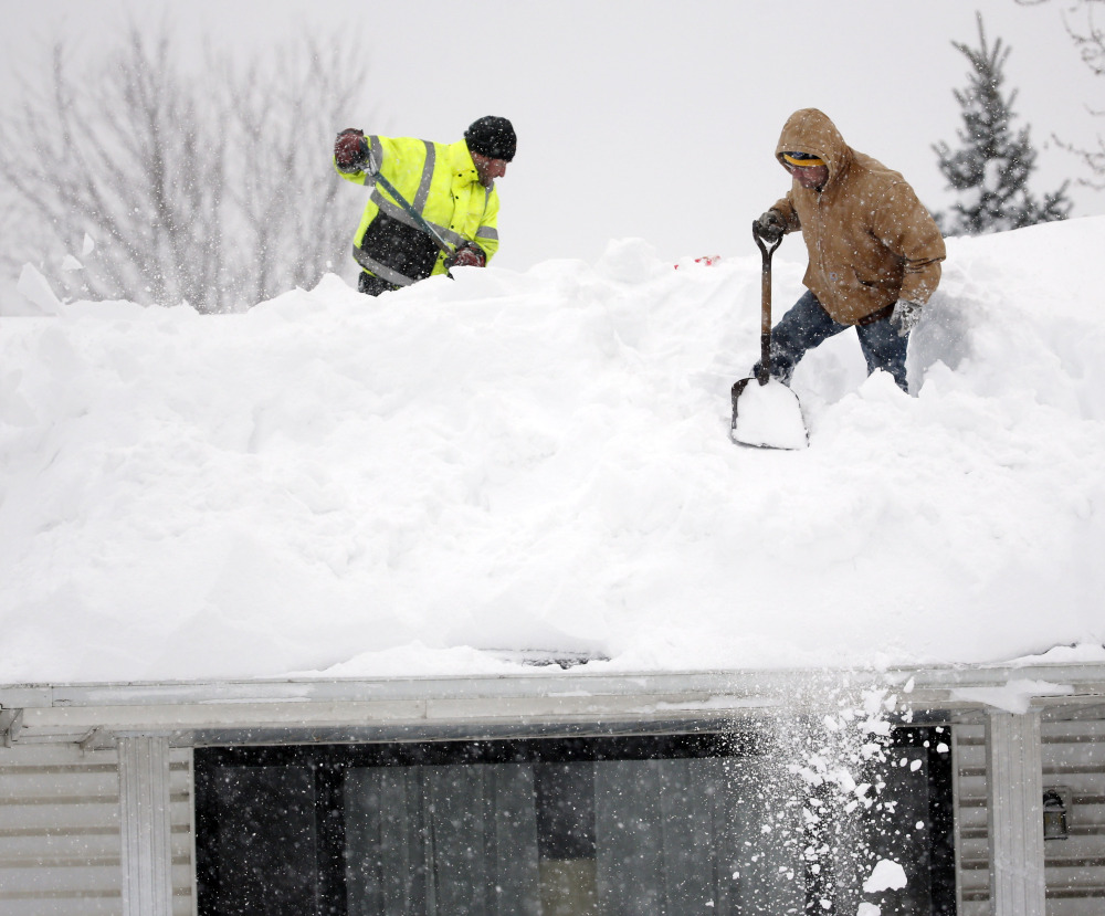 Mark Settlemyer, left, gets help from Ken Wesley clearing snow from the roof of his mother's house in Lancaster, N.Y., as residents worry about roofs buckling from the weight.