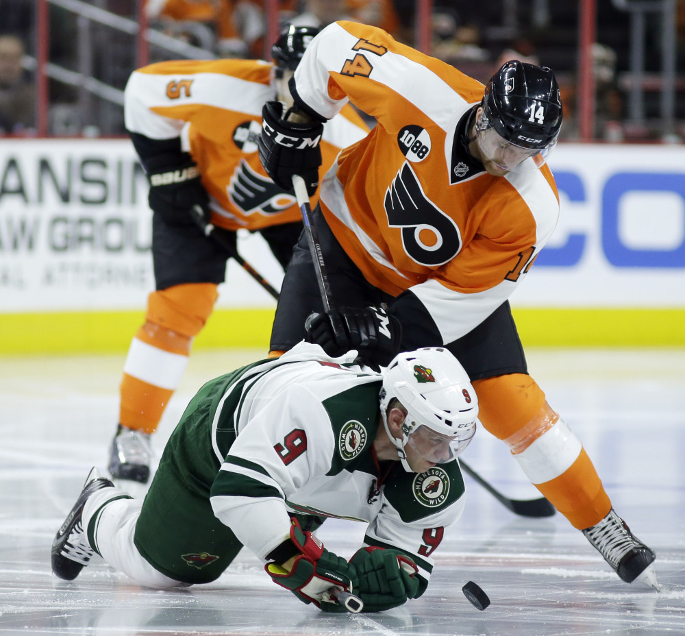 Without a stick, the Wild's Mikko Koivu battles for the puck with the Flyers' Sean Couturier during the second period of Thursday night's game in Philadelphia. Minnesota won 3-2 on Jason Zucker's goal in the final minute.