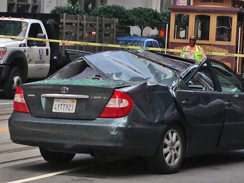 Police and citizens look over a car that has a caved-in roof after a window washer fell at least 11 stories onto the vehicle while it was making a turn in San Francisco on Friday.