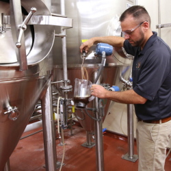 John Kimes, a MillerCoors pilot brewer, pours a sample of the Fred Miller chocolate lager in the fermenting and aging cellar.