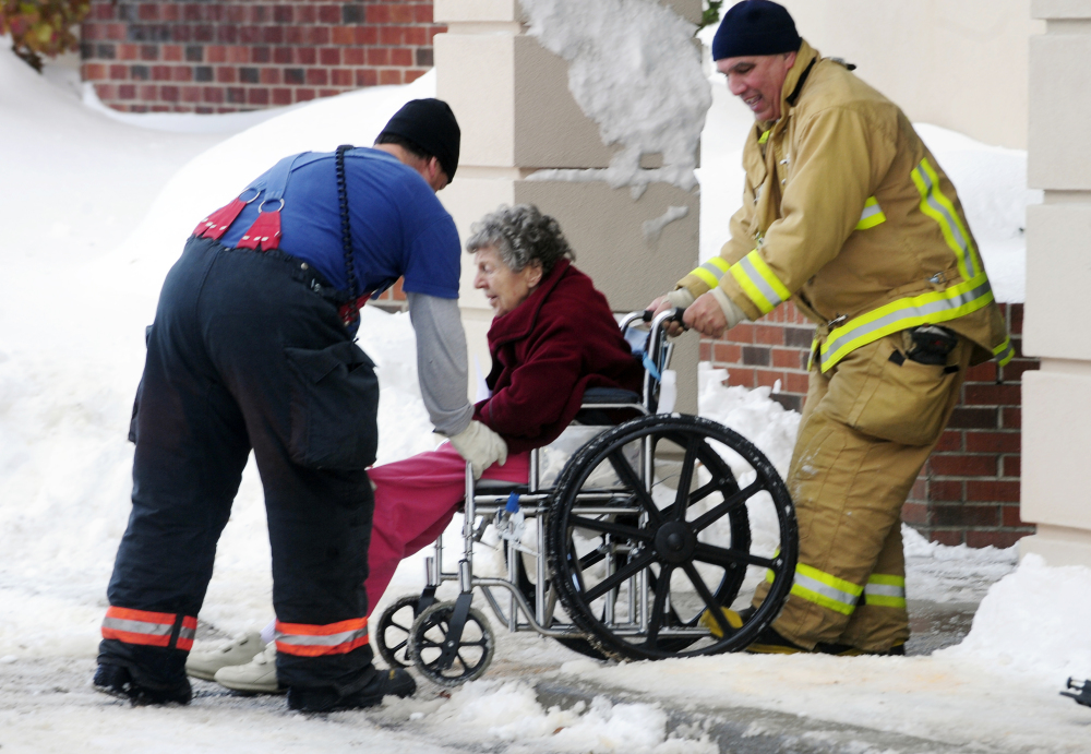 Firefighters assist an elderly patient from the Garden Gate Health Care Facility  in Cheektowaga, N.Y.