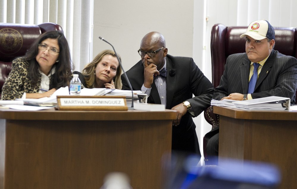 State Board of Education members, from left, Martha M. Dominguez, Donna Bahorich, Lawrence A. Allen Jr. and Ruben Cortez Jr. look toward other members during a recess on hearings Friday to approve textbooks in Austin, Texas.