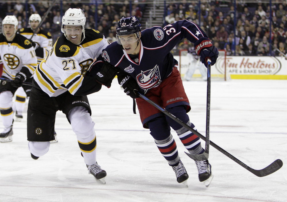 Boston Bruin Dougie Hamilton, front left, and Columbus' Adam Cracknell chase a loose puck during the second period of Friday night's game. The Bruins won in overtime, 4-3.