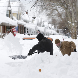 Mark Petrik and Dennis Smith dig out their driveway on Saturday in Buffalo, N.Y. Western New York continues to dig out from the heavy snow dropped by this week by lake-effect snowstorms.