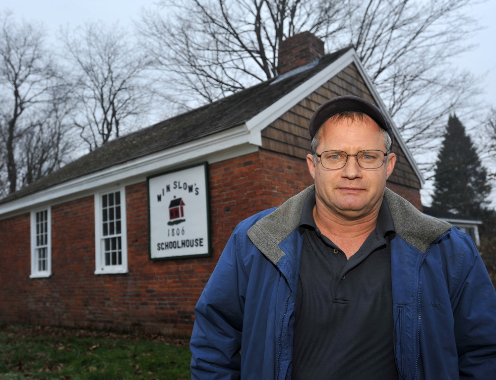 Winslow Councilman Raymond Caron, former vice president of the now defunct Winslow Historical Society, stands in front of the Winslow schoolhouse on Wednesday. He estimates that the town would need to budget $1,000 to $2,000 per year for the building's upkeep.