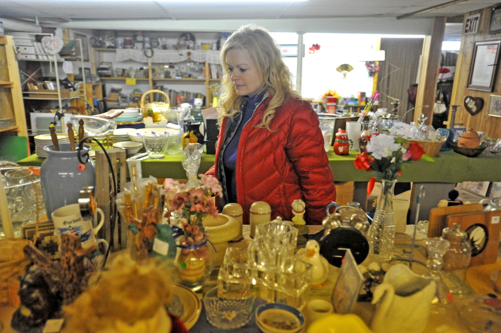 Susan Roy, executive director of Hospice Volunteers of Waterville Area, organizes donated merchandise in the resale shop.