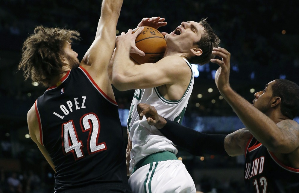 Portland's Robin Lopez fouls the Celtics' Tyler Zeller during the second period of Sunday's game in Boston, won by the Trail Blazers – the seventh straight victory for the NBA's Northwest Division leaders.
