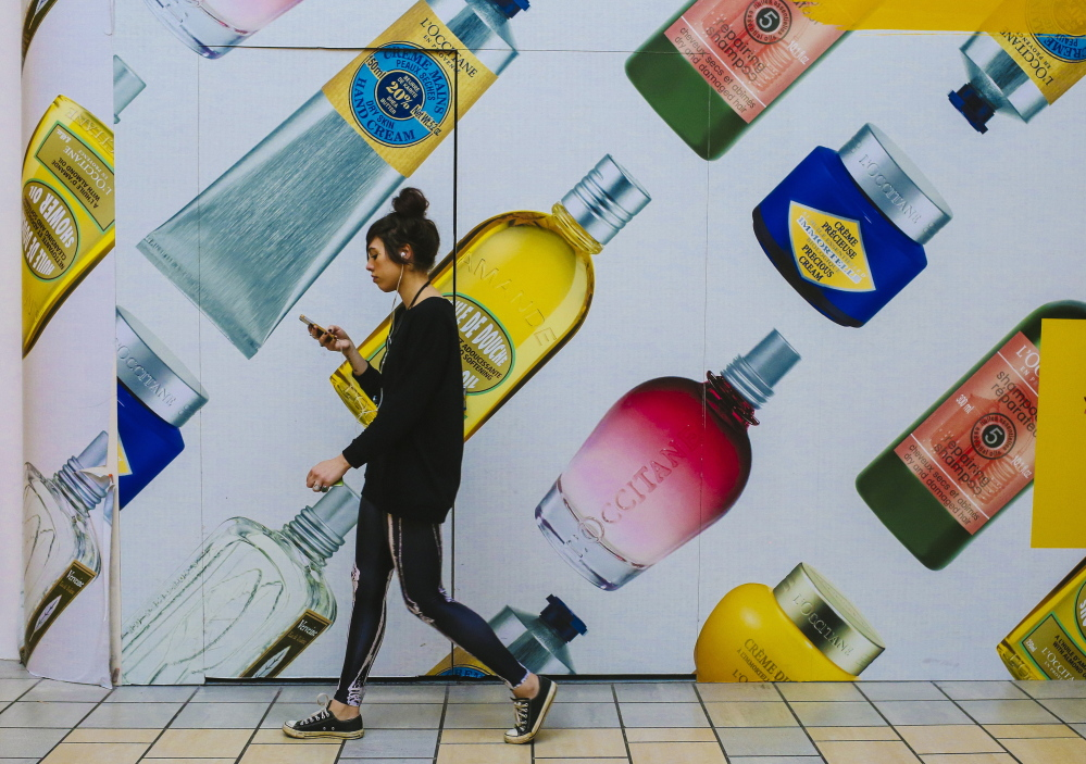 """Hannah Townsend walks Tuesday past a display for L'Occitane en Provence at The Maine Mall in South Portland. Townsend, who works at Newbury Comics in the mall, said she rarely shops on Black Friday because she often works that day, and because """"it's also too many people."""" An annual shopping study found that 41 percent of those surveyed plan to hit the stores on Black Friday."""