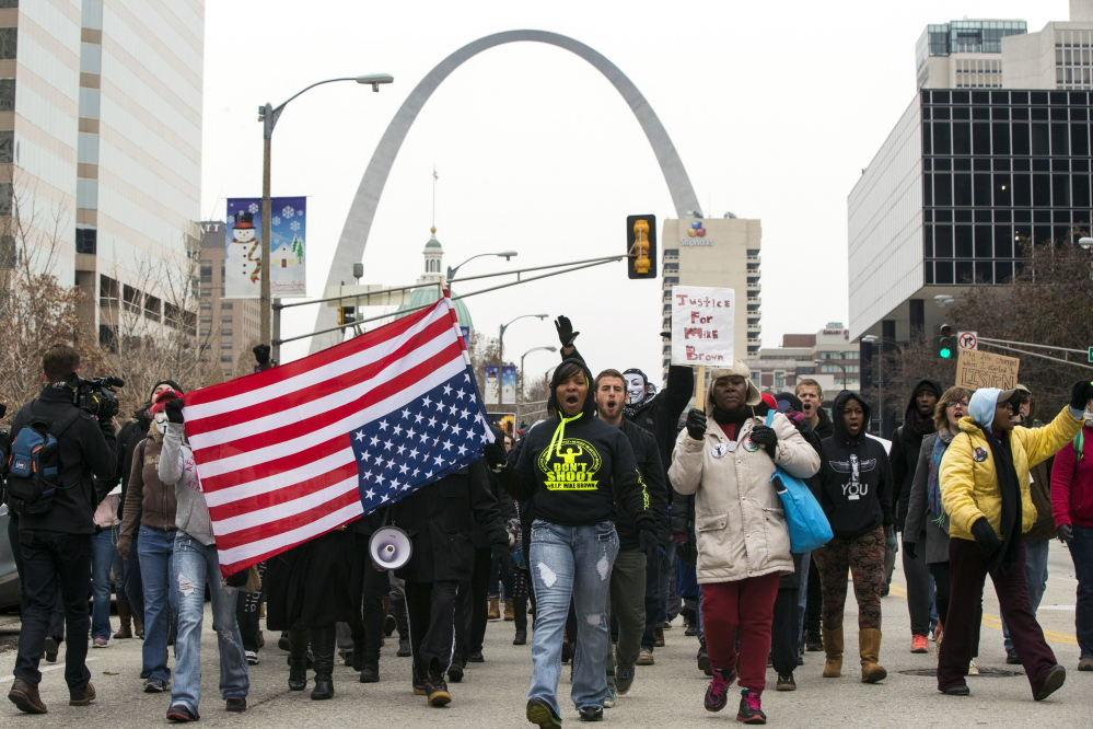 Demonstrators march to City Hall in St. Louis, Mo., on Wednesday as they protest a grand jury's decision not to indict white police officer Darren Wilson for killing unarmed black teenager Michael Brown, 18, in the St. Louis suburb of Ferguson.