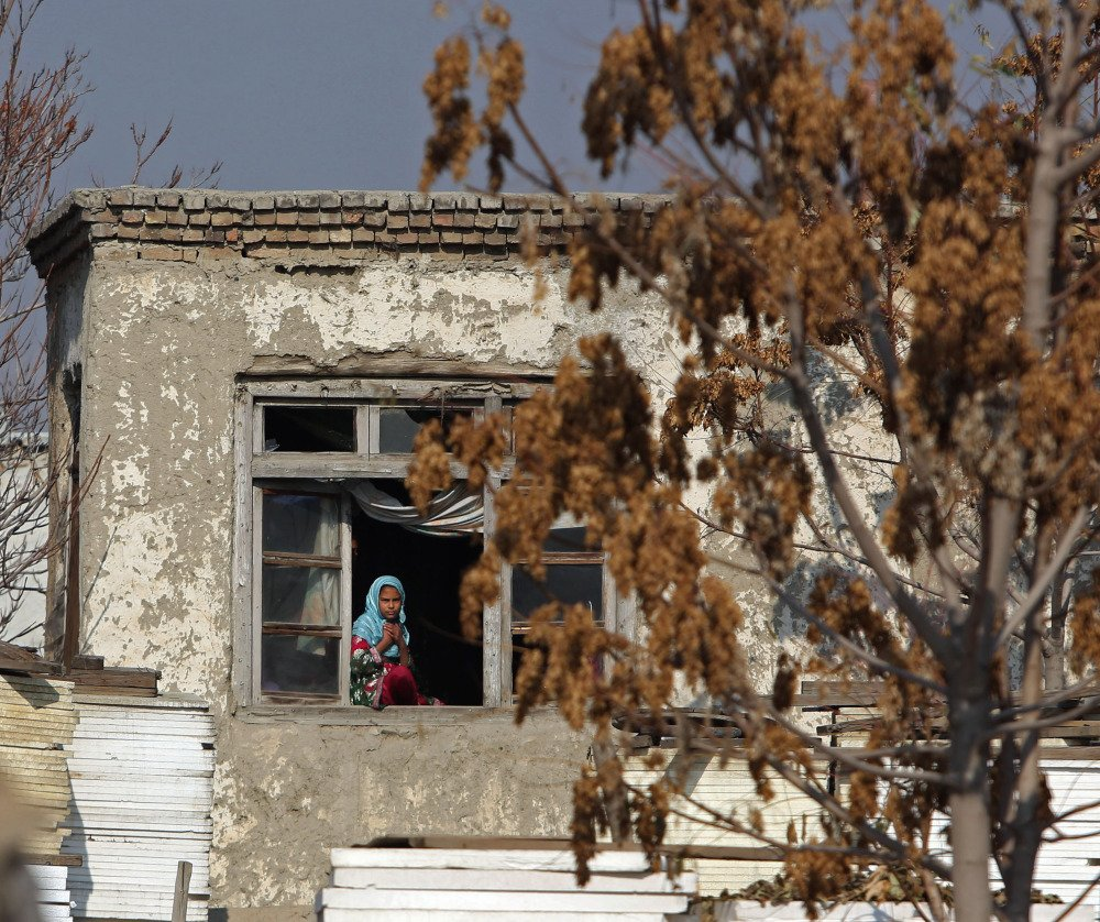 An Afghan girl looks out from her home near the site of a Taliban attack Thursday in Kabul. Attacks on international personnel and Afghan civilians have jumped in the past week.