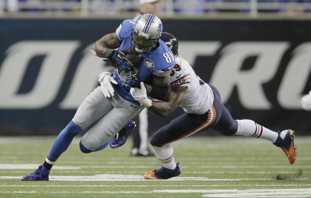 Chicago inside linebacker Christian Jones tackles Detroit wide receiver Calvin Johnson after his 9-yard reception Thursday in Detroit. With this catch, Johnson set an NFL record for fewest games (115) to reach 10,000 career receiving yards.