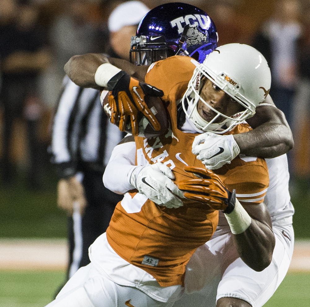 John Harris of Texas keeps a grip on the ball as he is hit by George Baltimore of Texas Christian during TCU's 48-10 win Thursday night. TCU remains in the hunt for a Big 12 title.