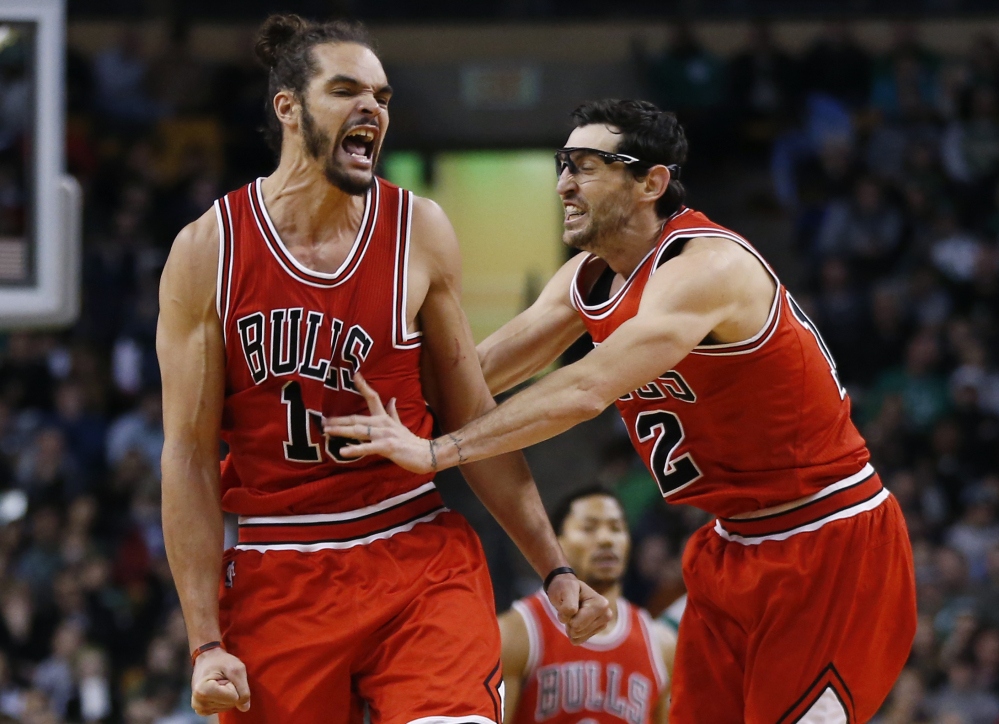 Chicago Bulls center Joakim Noah, left, celebrates with guard Kirk Hinrich (12) after making a crucial basket in the last minute against the Boston Celtics in Boston on Friday. The Associated Press
