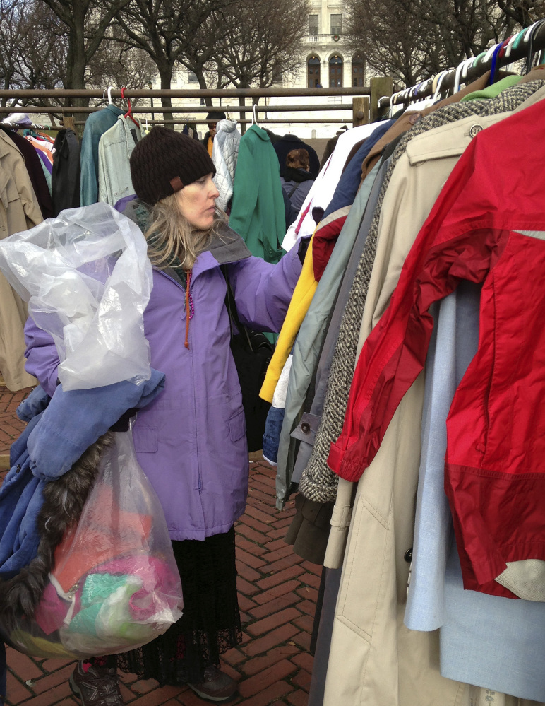 "Mary Frawley of Cranston, R.I., looks for a coat on the Statehouse lawn Friday in Providence, R.I. Winter coats were given away as part of the annual ""Buy Nothing Day."""