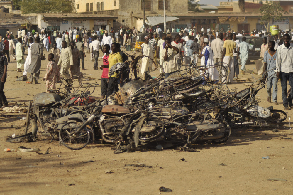 People gather at the site of a bombing in Kano, Nigeria, on Friday. Explosions tore through the central mosque in Nigeria's second-largest city, where hundreds had gathered to listen to a sermon in a region terrorized by attacks from Boko Haram.