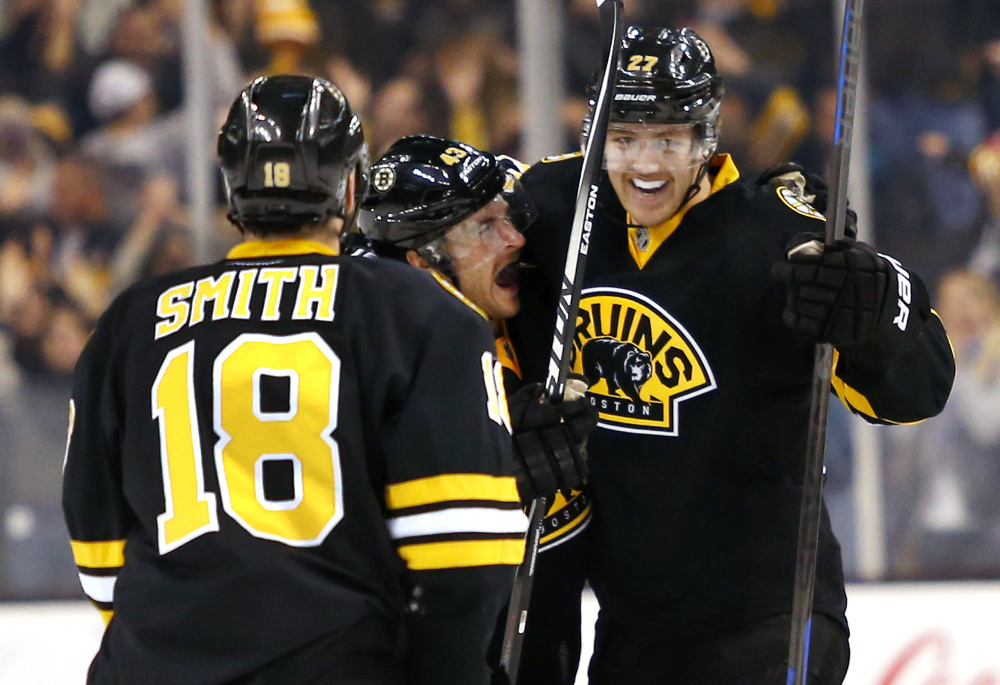 Boston Bruins defenseman Dougie Hamilton, right, celebrates his overtime goal with Matt Bartkowski and Reilly Smith, left, at the end of Friday night's game in Boston.