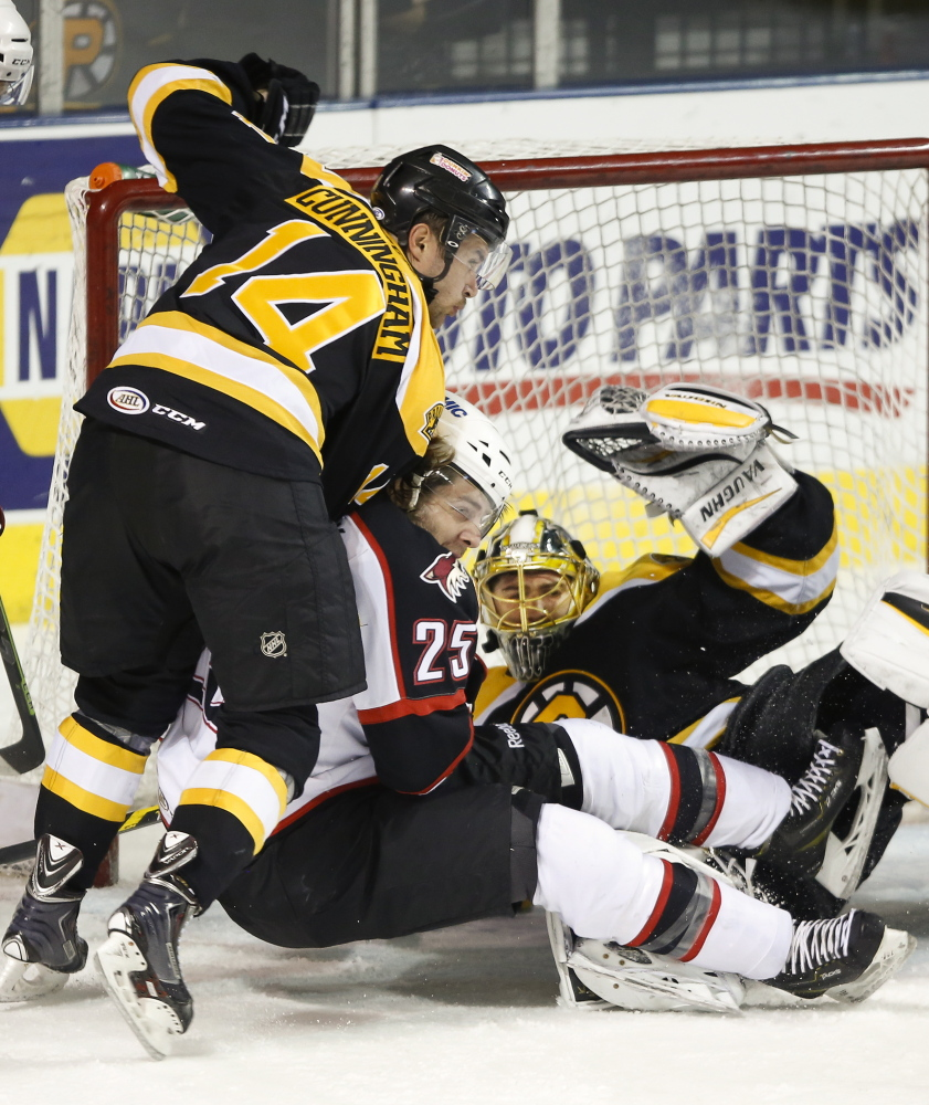 Eric Selleck of the Portland Pirates finds himself crunched between Craig Cunningham, left, and goalie Jeremy Smith of the Providence Bruins during their American Hockey League game Friday night. Portland emerged with a 3-2 overtime victory at the Cross Insurance Arena.