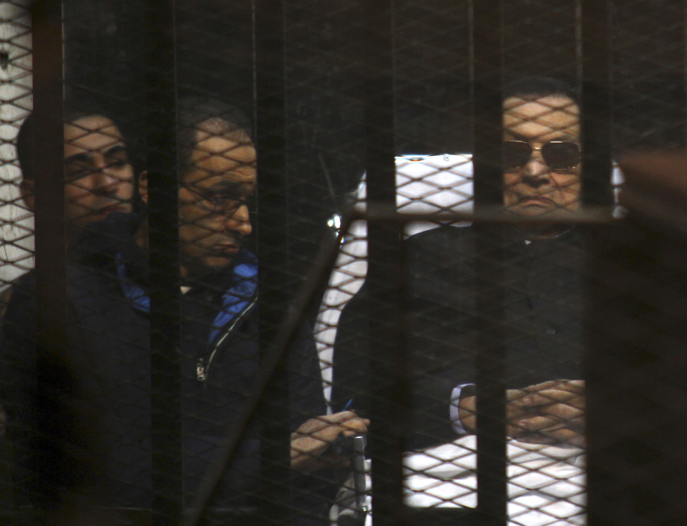 Ousted Egyptian President Hosni Mubarak, 86, lies on a gurney, next to his son, Gamal, second left, in the defendant's cage, during a court hearing in Cairo, Egypt, Saturday. An Egyptian court on Saturday dismissed murder charges against Mubarak in connection with the killing of protesters in the 2011 uprising that ended his nearly three-decade reign.