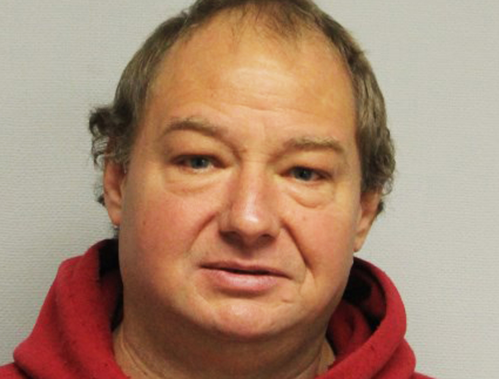 This undated photo provided by the Portsmouth Police Department, in New Hampshire, shows Roger Pelletier, who has been charged with felony counts of burglary and cruelty to animals, as well as simple assault after he tried to strangle his neighbor's barking dog but ended up getting bitten and arrested.