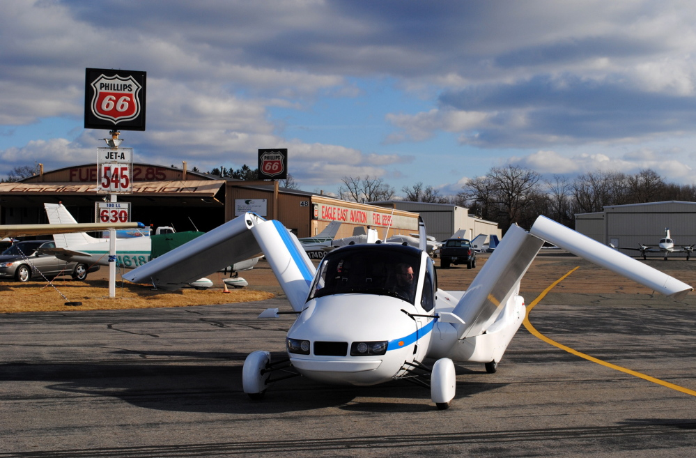 The Terrafugia Transition unfolds its wings at the Lawrence Municipal Airport in North Andover, Mass. It is designed to be driven on the road and to fly above traffic.
