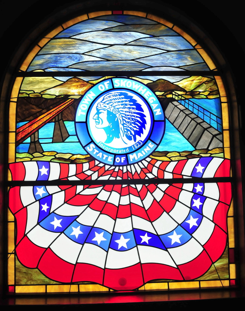 "This stained-glass window in the Skowhegan municipal building features images of the Kennebec River and an American Indian wearing a traditional headdress surrounded by the words ""Town of Skowhegan, State of Maine."""