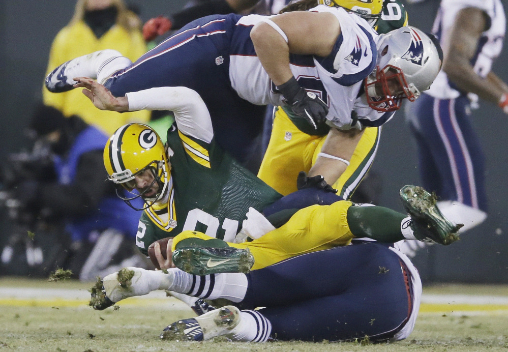 Green Bay Packers quarterback Aaron Rodgers is sacked by New England Patriots' Dont'a Hightower and Zach Moore (90) during the first half Sunday in Green Bay, Wis.