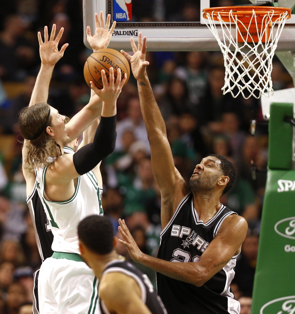 Boston's Kelly Olynyk, left, faces the shot-blocking defense of San Antonio's Tim Duncan during the Spurs' 111-89 win at Boston on Sunday.