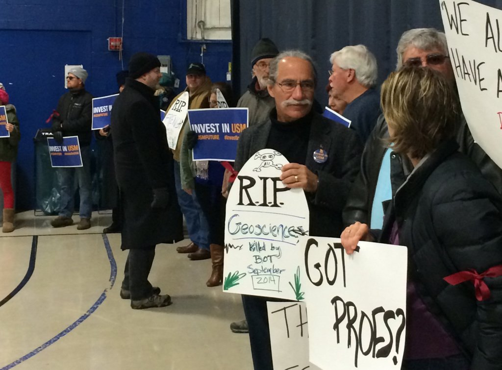 University of Southern Maine Faculty Senate Chairman Jerry Lasala, holding an RIP sigh, is among about 50 protesters who lined Sullivan Gym on the USM Portland campus, where the University of Maine System board of trustees met Sunday. Beth Quimby/Staff Writer