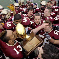 Thornton Academy's Corey Hart, 13, kisses the Gold Ball as he celebrates with his teammates after the Trojans beat Windham in the Class A football state championship. Gabe Souza/Staff Photographer