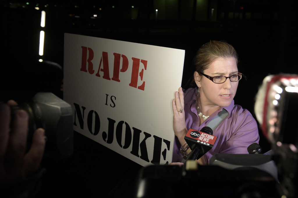 """Julie Lemaitre protests outside the Maxwell C. King Center for the Performing Arts in Melbourne, Fla., before Bill Cosby's performance Friday night. Lemaitre, 47, of Rockledge, Florida, said she protested just to have a presence and try to say to people at Friday's show """"think about what you're doing."""""""