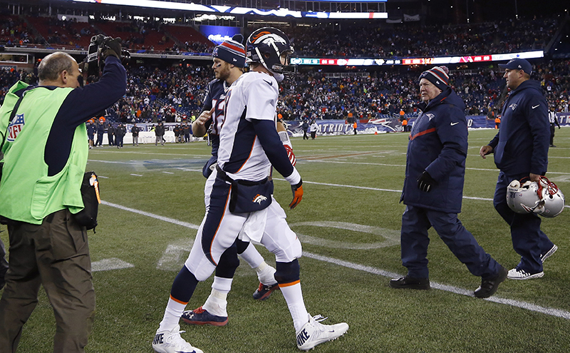 New England Patriots quarterback Tom Brady, left, and Denver Broncos quarterback Peyton Manning head to their respective locker rooms after an NFL football game on Sunday, The Associated Press