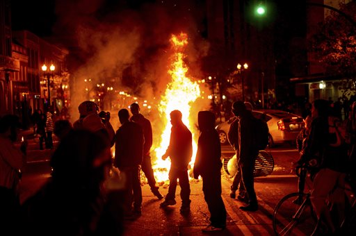 Protesters gather around burning refuse in Oakland, Calif., on Tuesday after the announcement that a grand jury decided not to indict Ferguson police officer Darren Wilson in the fatal shooting of Michael Brown, an unarmed 18-year-old. Several thousand protesters marched through Oakland with some shutting down freeways, looting, burning garbage and smashing windows. The Associated Press