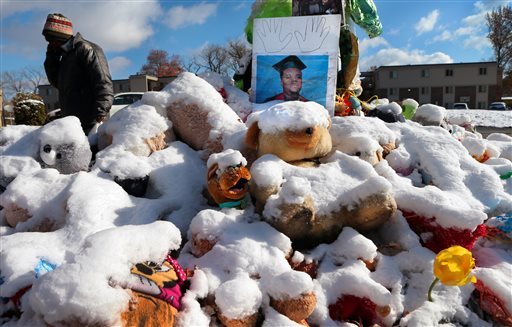 A high school graduation photo of Michael Brown rests on top of a snow-covered memorial on Monday, more than three months after the teen was shot and killed nearby by a white policeman in Ferguson, Mo. The Associated Press