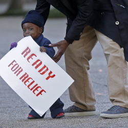 Lavon Massey, 1, holds a sign as immigrants and activists hold a protest outside the U.S. Citizenship & Immigration Service office in New Orleans. The event was  to draw attention to the possibility that many immigrants living illegally in the United States may not be shielded by an executive order President Barack Obama is expected to sign. The Associated Press
