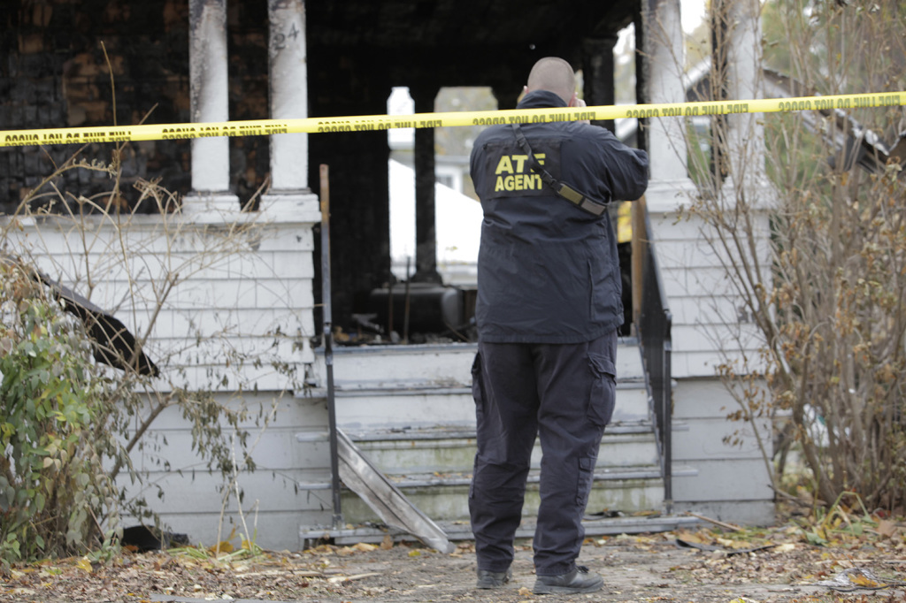 An agent with the Bureau of Alcohol, Tobacco, Firearms and Explosives photographs the house at 20 Noyes St. in Portland Monday. Investigators are still trying to determine the cause.