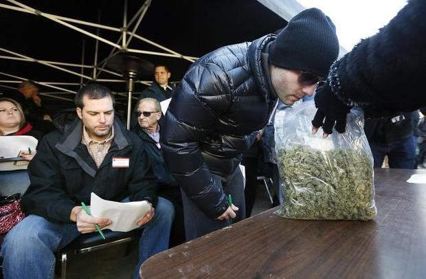 Leo Gontmakher, a marijuana processor with Northwest Cannabis Solutions in Sultan, Washington, smells a bag of marijuana during the auction at Fireweed Farms in Prosser. The Associated Press