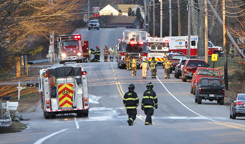 Firefighters from Biddeford and Saco clean up at the scene of a fire on Route 111 in Biddeford on Friday morning. The fire closed the road during the morning commuting hours.