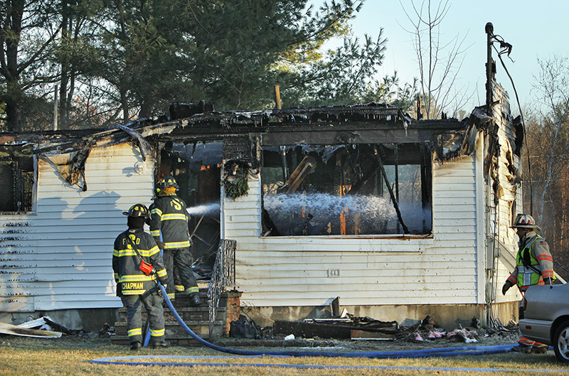 Saco firefighters douse hot spots in a building on Alfred Road in Biddeford that caught fire on Friday morning.