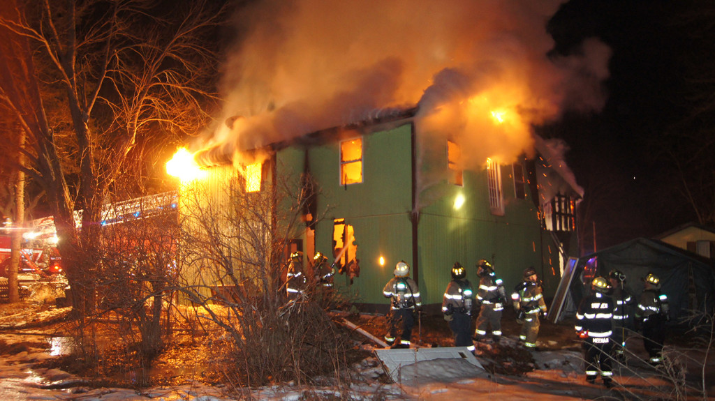 Firefighters from Bridgton and neighboring towns fight a fire Monday night that destroyed a garage and caused smoke and fire damage to a portion of the adjacent house.