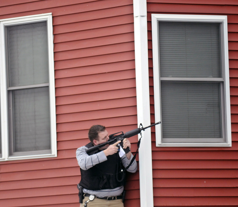 Augusta Police Detective Chris Blodgett aims a rifle Tuesday into a second-floor apartment at 388 Water St. in Augusta as members of the department's tactical team apprehend Lorne Sherwood. Andy Molloy/Kennebec Journal