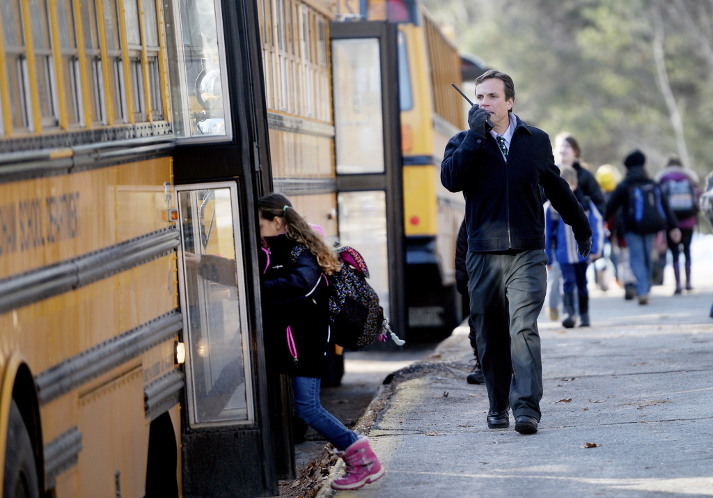 Windham Primary School Principal Kyle Rhoads talks on a radio as students board buses to leave school Monday morning after a threatening email message prompted Regional School Unit 14 to release students from all of its schools in Windham and Raymond. The schools will be closed again Tuesday.