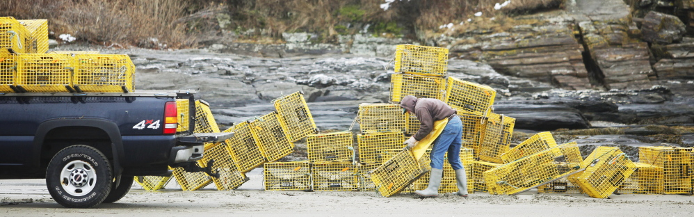 Ed Perry, a commercial lobsterman for 30 years, stacks lobster traps into his truck on the beach at Kettle Cove in Cape Elizabeth on Sunday. The process began Saturday as the traps were dropped off his boat into the water at high tide, and then stacked and picked up at low tide Sunday.