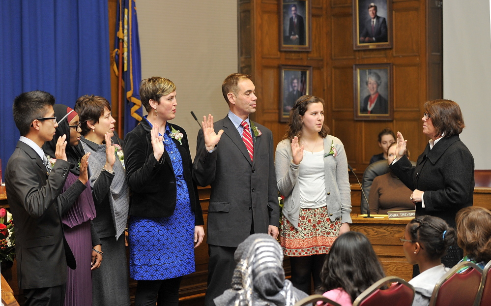 Portland City Clerk Katherine Jones, right, performs the swearing-in of newly elected and re-elected School Board members at Portland City Hall on Monday.