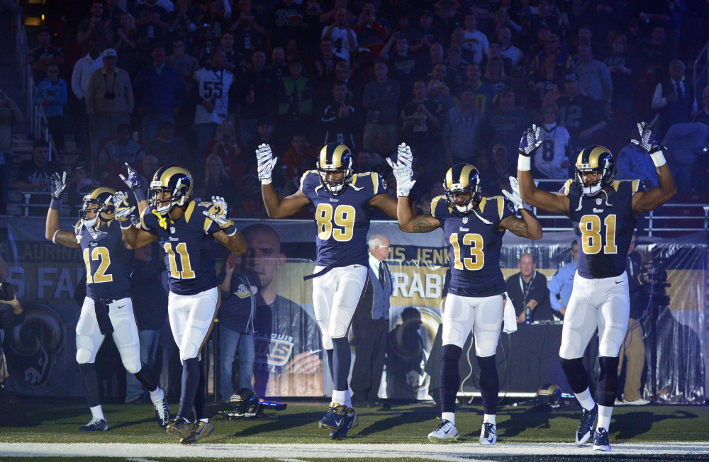 "St. Louis players, from left, Stedman Bailey, Tavon Austin, Jared Cook, Chris Givens and Kenny Britt take the field with a ""Hands Up., Don't Shoot!"" gesture before Sunday's game against Oakland in St. Louis. The players say they were showing their support for the community."