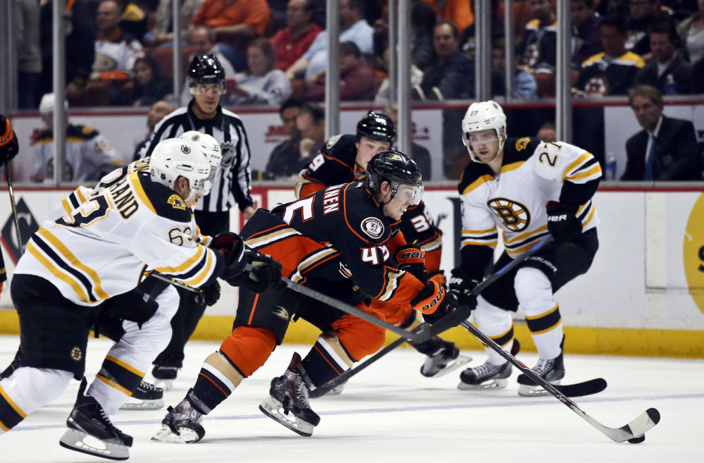 Anaheim defenseman Sami Vatanen breaks through the defense of the Boston Bruins' Brad Marchand, left, during the second period of Monday night's game in Anaheim, Calif.