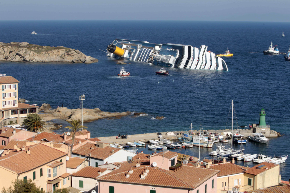 In this Saturday, Jan. 14, 2012 file photo, the luxury cruise ship Costa Concordia leans on its starboard side off the port at Giglio, after running aground on the tiny Tuscan island of Giglio, Italy.