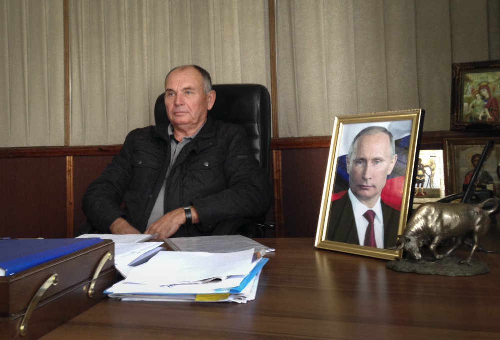In this photo taken on Wednesday, Oct.  22, 2014, quail egg farmer Mikhail Sirotyuk speaks to the Associated Press in an interview in Trudovoe, Crimea. Sirotyuk, whose office in the rural village of Trudovoe is decorated with two portraits of Putin and three religious icons, has changed the locks out of fear of what might happen next.