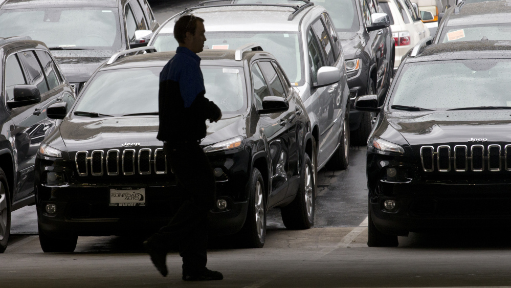 A worker on a Chrysler car lot passes rows of parked vehicles – most of them Jeep SUVs – on Tuesday in San Diego. Chrysler has posted its best November in 13 years.